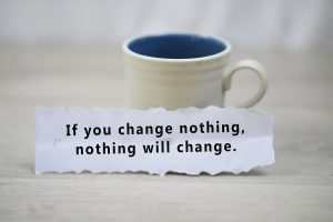 Coffee cup by a piece of paper that says if you change nothing, nothing will change. Get online therapy for imposter syndrome with melissa russiano. Start online therapy in florida, online therapy in tennessee, online therapy in ohio, and online therapy in pennsylvania