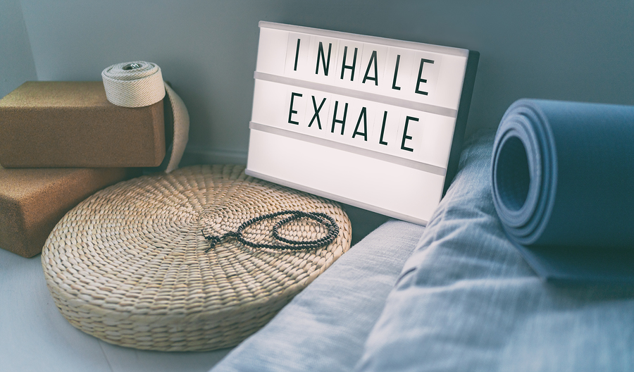 photo of a yoga room next to a light sign that says inhale exhale. This represents the self care skills you'll learn when working with online therapist Melissa russiano who offers online anxiety therapy in Ohio, online anxiety therapy in Pennsylvania, online anxiety therapy in tennessee, online anxiety therapy in florida, and online anxiety therapy in California to help treat therapist burnout and anxiety