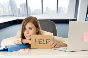 photo of a woman holding a sign that says help in front of her computer. She works with melissa russiano who offers online therapy for busy professionals and therapy for therapists, online therapy in florida, online therapy in california, online therapy in pennsylvania, online therapy in ohio, online therapy in tennessee